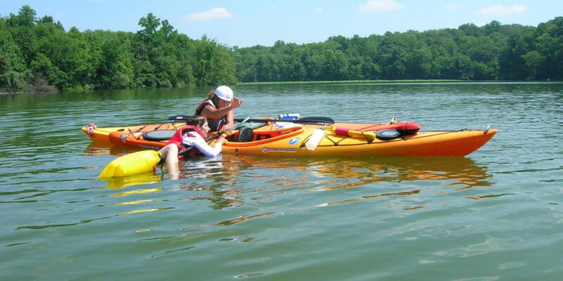 kayakers preforming self rescue with paddle float