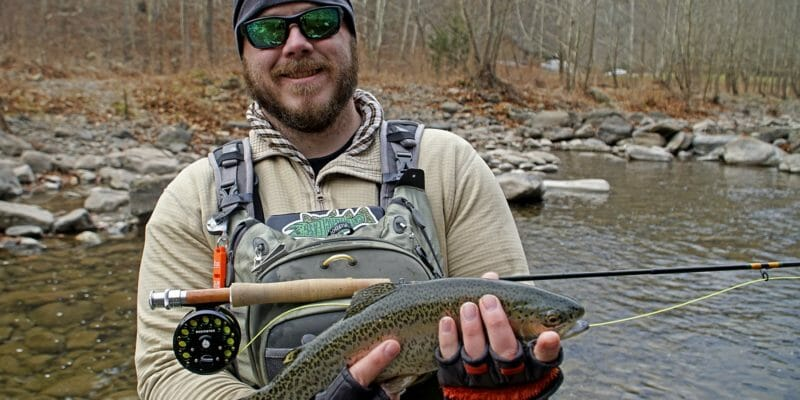 angler wearing bibs holding trout