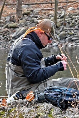 angler tying knot wearing cold weather fishing bibs